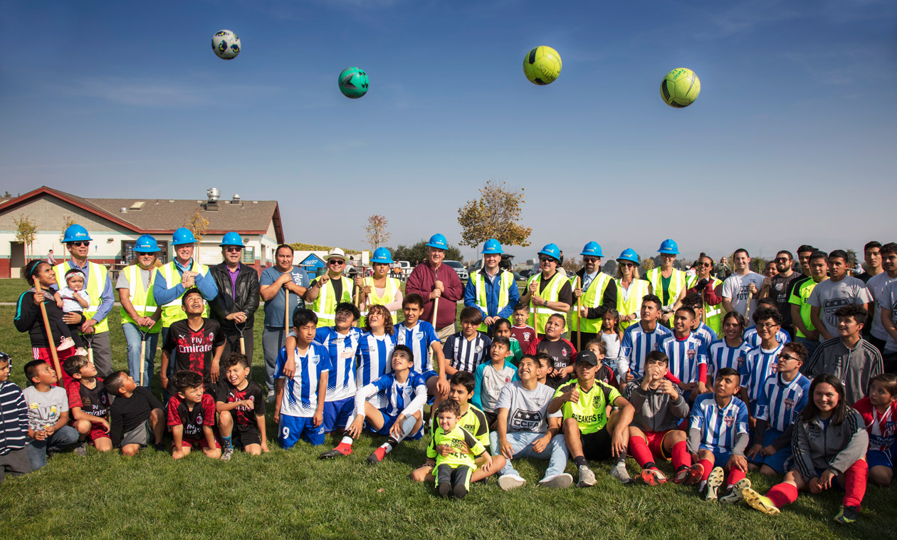 Group of soccer enthusiasts with 4 balls in the air.